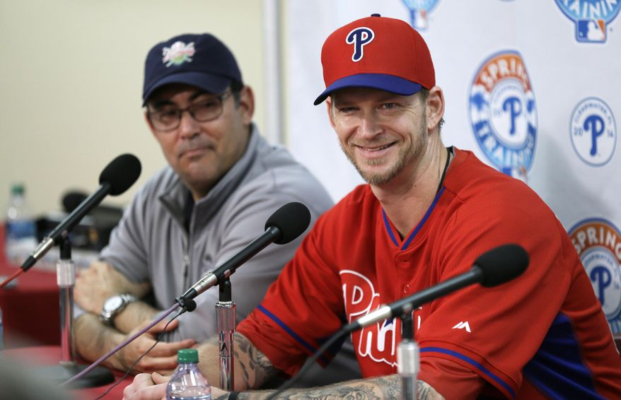Philadelphia Phillies pitcher A.J. Burnett, right, speaks during a news conference as Phillies general manager Ruben Amaro Jr., left, looks on following a spring training baseball practice on Sunday, Feb. 16, 2014, in Clearwater, Fla. (AP Photo/Charlie Neibergall)