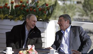 Russian President Vladimir Putin, left, and International Olympic Committee President Thomas Bach sit at a cafe along the promenade on the Black Sea near the Olympic Park at the 2014 Winter Olympics, Saturday, Feb. 15, 2014, in Sochi, Russia. (AP Photo/David Goldman)