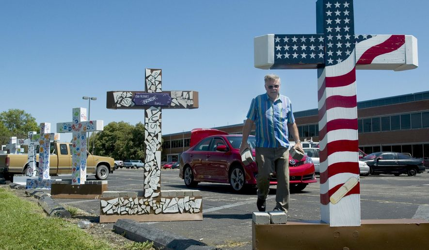 In this August 14, 2013 photo, Roger Lehman, an elder with West Side Christian Church in Evansville, hauls bricks to help anchor the lightweight, plastic crosses, part of the Cross the River display, from the parking lot of the old Whirlpool plant in Evansville, Ind. The lightweight, plastic crosses were no match for the gusty winds and were continually blown over. The Seventh Circuit Court of Appeals has scheduled a Feb. 18, 2014 hearing in Chicago to hear arguments in the West Side Christian Church's appeal of a judge's decision blocking a planned display of 6-foot tall crosses at the city's public riverfront.  (AP Photo/The Evansville Courier & Press, Denny Simmons)