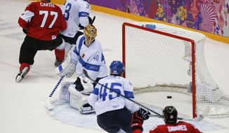 Finland goaltender Tuukka Rask watches as the puck bounces out of the net on a sudden death overtime goal by Canada defenseman Drew Doughty during a men's ice hockey game at the 2014 Winter Olympics, Sunday, Feb. 16, 2014, in Sochi, Russia. Canada won 2-1. (AP Photo/Julio Cortez)