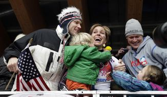 ADD ID OF MAN ON LEFT - Noelle Pikus-Pace of the United States celebrates with her brother Jared Pikus, left, husband, Janson Pace, right, and her children, Traycen, left, and Lacee, lower right, after she won the silver medal during the women's skeleton competition at the 2014 Winter Olympics, Friday, Feb. 14, 2014, in Krasnaya Polyana, Russia. (AP Photo/Michael Sohn)