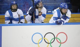 Rosa Lindstedt of Finland, center, wipes away a tear as she sits on the bench with teammates Tea Villila, left, and Anna Kilponen, right after their 4-2 loss to Sweden in the 2014 Winter Olympics women's ice hockey quarterfinal game at Shayba Arena, Saturday, Feb. 15, 2014, in Sochi, Russia. (AP Photo/Matt Slocum)