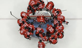 Team Switzerland huddles around the net before their game against Latvia during the 2014 Winter Olympics men's ice hockey game at Shayba Arena, Wednesday, Feb. 12, 2014, in Sochi, Russia. (AP Photo/Julio Cortez)