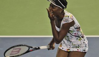 Venus Williams of the U.S. reacts after she missed a ball to Elena Vesnina of Russia during the first round of Dubai Duty Free Tennis Championships in Dubai, United Arab Emirates, Monday, Feb. 17, 2014. (AP Photo/Kamran Jebreili)