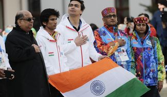 Newly elected Indian Olympic Association President Narayna Ramachandran, left, and members of the Indian Olympic team, alpine skier Thakur Himanshu, second left, and luger Shiva Keshavan, center, listen to the Indian national anthem during a welcome ceremony at the Mountain Olympic Village on Sunday, Feb. 16, 2014, during the 2014 Winter Olympics in Krasnaya Polyana, Russia. (AP Photo/Jae C. Hong)
