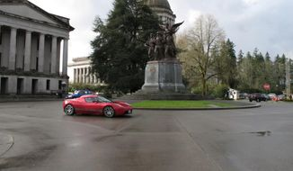 A Tesla car drives near the Washington state Capitol on Monday, Feb. 17, 2014, in Olympia, Wash. The electric car company, which has sales and service operations in Seattle and Bellevue, held a rally to protest measures being considered by the Legislature that would prevent it from opening additional facilities in the state. (AP Photo/Rachel La Corte)