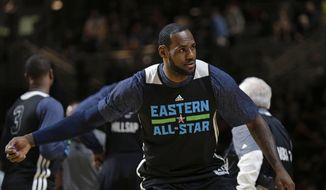 East Team's LeBron James, of the Miami Heat, throws a pair of Mardi Gras beads to the crowd during NBA All-Star game basketball practice in New Orleans, Saturday, Feb. 15, 2014. (AP Photo/Gerald Herbert)