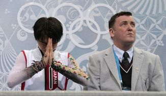 Yuzuru Hanyu of Japan, left, reacts alongside his coach Brian Orser as he sits in the results area after the men's free skate figure skating final at the Iceberg Skating Palace at the 2014 Winter Olympics, Friday, Feb. 14, 2014, in Sochi, Russia. (AP Photo/Ivan Sekretarev)