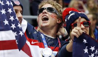 U.S. fans cheer as Russia and the USA take the ice before playing in a men's ice hockey game at the 2014 Winter Olympics, Saturday, Feb. 15, 2014, in Sochi, Russia. (AP Photo/Mark Humphrey)