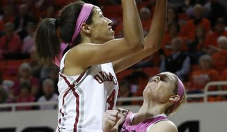 Oklahoma center Nicole Griffin, left, fouls Oklahoma State forward Liz Donohoe, right, while shooting in the first half of an NCAA college basketball game in Stillwater, Okla., Sunday, Feb. 16, 2014. (AP Photo/Sue Ogrocki)