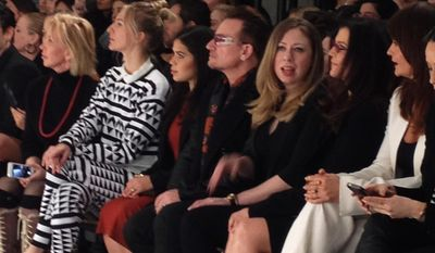 This Feb. 9, 2014 file photo shows Chelsea Clinton between singer Bono, center, and his wife Ali Hewson, co-founders of the Edun line, in the front row of the Edun runway show during New York Fashion Week in New York. (AP Photo/Leanne Italie, File)