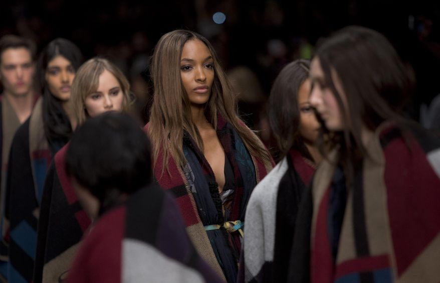 Model Jourdan Dunn, centre, wears a design created by Burberry Prorsum Womenswear during London Fashion Week Autumn/Winter 2014, at Perks Field, Kensington Palace, in Hyde Park, central London, Monday, Feb. 17, 2014. (Photo by Joel Ryan/Invision/AP)