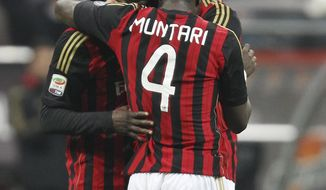 AC Milan forward Mario Balotelli, left, celebrates with his teammates Sulley Muntari, center, of Ghana, and Adil Rami, of France, after scoring during the Serie A soccer match between AC Milan and Bologna at the San Siro stadium in Milan, Italy, Friday, Feb. 14, 2014. (AP Photo/Antonio Calanni)