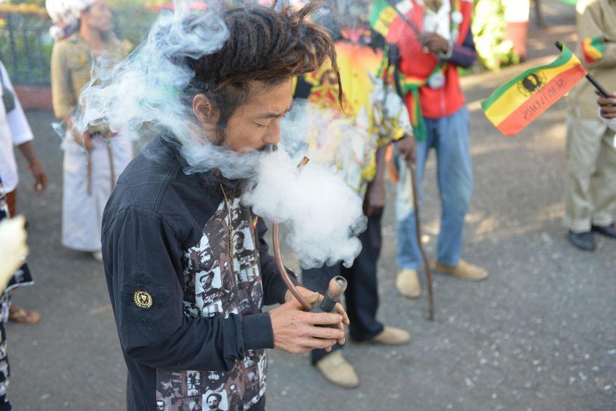 In this Feb. 6, 2013, photo, a Rastafarian named Bongho Jatusy smokes a pipe of marijuana outside a museum dedicated to the memory of late reggae icon Bob Marley in Kingston, Jamaica. (AP Photo/David McFadden, File)