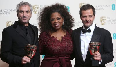 From left, Alfonso Cuaron, Oprah Winfrey and David Heyman, winners of outstanding British film for Gravity, pose for photographers in the winners room at the EE British Academy Film Awards held at the Royal Opera House on Sunday Feb. 16, 2014, in London. (Photo by Joel Ryan/Invision/AP)
