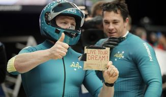 """The team from Australia AUS-1, piloted by Heath Spence and brakeman Duncan Harvey, hold up a sign that says """"Live Your Dream,"""" after their third run during the men's two-man bobsled competition at the 2014 Winter Olympics, Monday, Feb. 17, 2014, in Krasnaya Polyana, Russia. (AP Photo/Jae C. Hong)"""