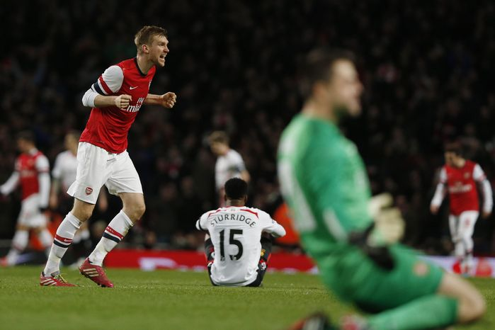Arsenal's Per Mertesacker, left, and goalkeeper Lukasz Fabianski, right foreground, celebrate their win as Liverpool's Daniel Sturridge, center, sits on the ground at the end of their English FA Cup fifth round soccer match at Emirates Stadium in London, Sunday, Feb. 16, 2014. (AP Photo/Sang Tan)