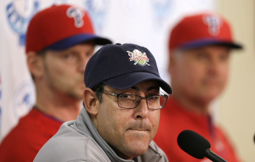 Philadelphia Phillies general manager Ruben Amaro Jr., center, speaks during a news conference as pitcher A.J. Burnett, left, and manager Ryne Sandberg, right, look on following a spring training baseball practice on Sunday, Feb. 16, 2014, in Clearwater, Fla. (AP Photo/Charlie Neibergall)