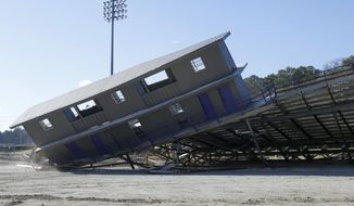 The press box and part of the stands fall to the ground at A.U. Williams Field at Ouachita Baptist University in Arkadelphia, Ark., Friday, Feb. 14, 2014. The stands were demolished to make way for the new Cliff Harris Stadium to be constructed in time for the fall 2014 NCAA college football season. (AP Photo/Danny Johnston)