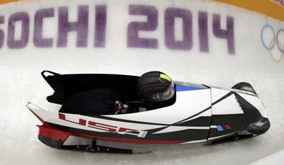 Jazmine Fenlator and Lolo Jones of the United States take a turn during a training session for the women's bobsleigh at the 2014 Winter Olympics,  Sunday, Feb. 16, 2014, in Krasnaya Polyana, Russia. (AP Photo/Michael Sohn)