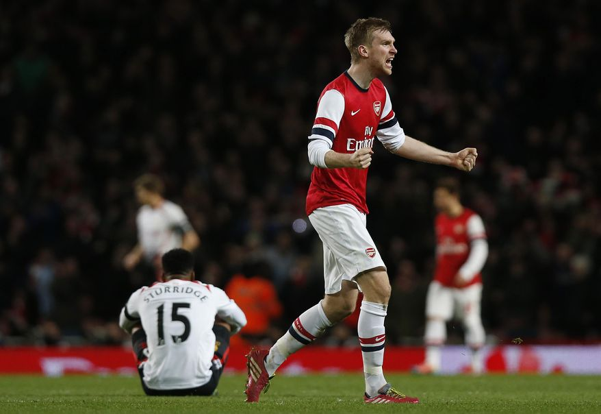 Arsenal's Per Mertesacker celebrates their win against Liverpool at the end of their English FA Cup fifth round soccer match at Emirates Stadium in London, Sunday, Feb. 16, 2014. (AP Photo/Sang Tan)