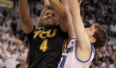 CORRECTS DATE - VCU's Terrance Shannon (4) puts up a shot as Saint Louis' Rob Loe (51) defends in the first half of an NCAA college basketball game, Saturday, Feb. 15, 2014, in St. Louis.(AP Photo/Tom Gannam)