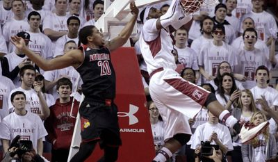 Louisville's Wayne Blackshear (20) defends as Temple's Anthony Lee scores during the first half of an NCAA college basketball game, Friday, Feb. 14, 2014, in Philadelphia. (AP Photo/H. Rumph Jr.)