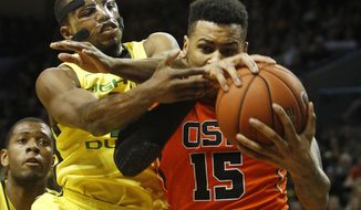 With teammate Mike Moser, left, looking on, Oregon's Johnathan Loyd, center, battles Oregon State's Eric Moreland for a rebound during the second half an NCAA college basketball game in Eugene, Ore., Sunday, Feb. 16, 2014. (AP Photo/Chris Pietsch)