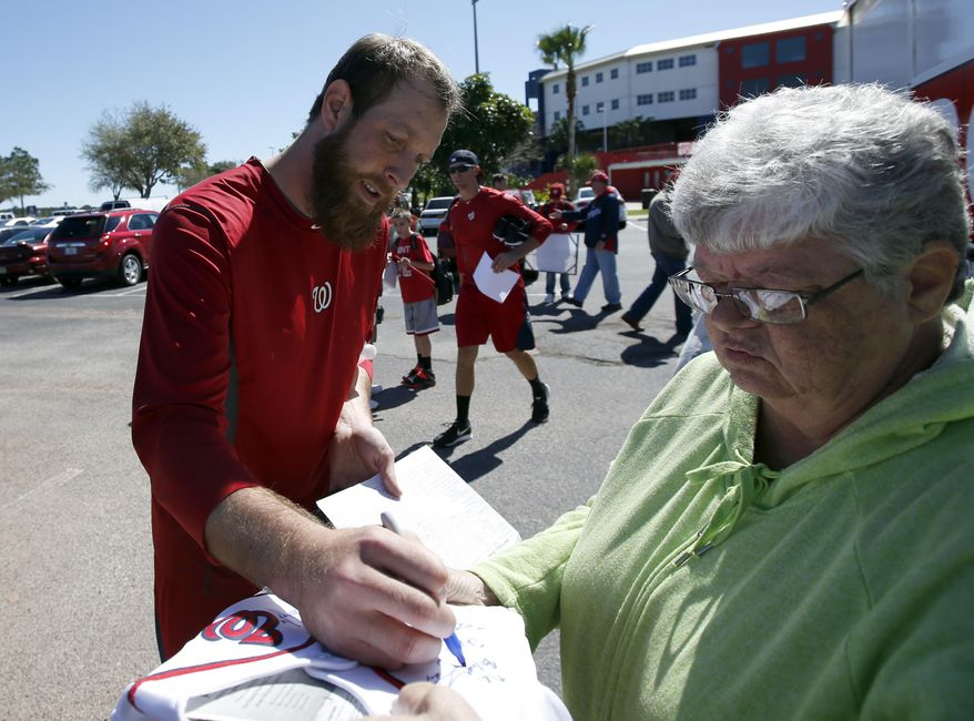 Washington Nationals relief pitcher Ryan Mattheus signs an autograph for a fan during a break in their spring training baseball workout, Friday, Feb. 14, 2014, in Viera, Fla. (AP Photo/Alex Brandon)