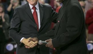 Former President Bill Clinton, left, and Nolan Richardson, right, greet each other during halftime of an NCAA college basketball game between Arkansas and LSU on Saturday, Feb. 15, 2014, in Fayetteville, Ark. (AP Photo/Gareth Patterson)