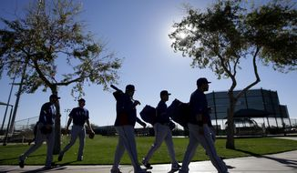 Texas Rangers pitchers and catchers arrive to the practice field for workouts during spring training baseball practice, Monday, Feb. 17, 2014, in Surprise, Ariz. (AP Photo/Tony Gutierrez)