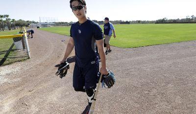 Tampa Bay Rays shortstop Hak-Ju Lee, of South Korea, steps off the field following spring training baseball practice Friday, Feb. 14, 2014, in Port Charlotte, Fla. (AP Photo/Steven Senne)
