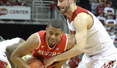 Louisville's Luke Hancock, right, battles Rutgers' Jerome Seagears for the ball during the first half of an NCAA college basketball game on Sunday, Feb. 16, 2014, in Louisville, Ky. (AP Photo/Timothy D. Easley)