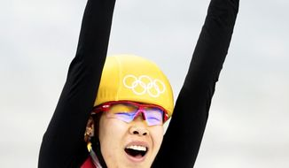 Zhou Yang of China celebrates as she crosses the finish line first in a women's 1500m short track speedskating final at the Iceberg Skating Palace during the 2014 Winter Olympics, Saturday, Feb. 15, 2014, in Sochi, Russia. (AP Photo/Ivan Sekretarev)