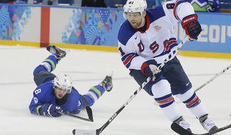 USA forward Phil Kessel take the puck away from Slovenia forward Ziga Jeglic during the 2014 Winter Olympics men's ice hockey game at Shayba Arena Sunday, Feb. 16, 2014, in Sochi, Russia. (AP Photo/Matt Slocum)