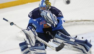 Goalkeeper Noora Raty of Finland blocks a shot on the goal during the second period of the 2014 Winter Olympics women's ice hockey game against Switzerland at Shayba Arena, Wednesday, Feb. 12, 2014, in Sochi, Russia. (AP Photo/Petr David Josek)