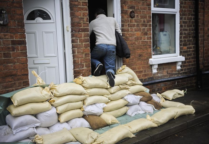 A local resident climbs over a sandbag levee protecting the front doors of homes in Gloucester, southwest England, as the region reacts to an increased flood threat alert Friday Feb. 14, 2014.  Many regions of Britain have been warned to expect severe weather over the coming days from heavy rainfall, gale-force winds and snow.(AP Photo/Ben Birchall, PA) UNITED KINGDOM OUT - NO SALES - NO ARCHIVES