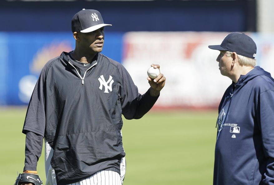 New York Yankees starting pitcher CC Sabathia, left, talks with pitching coach Larry Rothschild, right, during spring training baseball practice Friday, Feb. 14, 2014, in Tampa, Fla. (AP Photo/Charlie Neibergall)