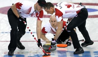 Canada's Ryan Fry delivers the rock while Ryan Harnden, left, and E.J. Harnden, right, sweep the ice during the men's curling match against the United States at the 2014 Winter Olympics, Sunday, Feb. 16, 2014, in Sochi, Russia. (AP Photo/Wong Maye-E)