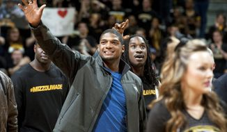 Missouri's All-American defensive end Michael Sam waves to the crowd during the Cotton Bowl trophy presentation at halftime of an NCAA college basketball game between Missouri and Tennessee, Saturday, Feb. 15, 2014, in Columbia, Mo. Sam came out to the entire country Sunday, Feb. 9, and could become the first openly gay player in the NFL. (AP Photo/L.G. Patterson)