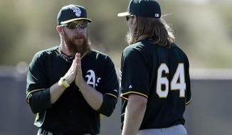 Oakland Athletics pitcher Sean Doolittle, left, talks with pitcher A.J. Griffin during spring training baseball practice on Saturday, Feb. 15, 2014, in Scottsdale, Ariz. Doolittle is scheduled to be held out of bullpen sessions for few days because of a right calf strain, according to Athletics manager Bob Melvin. (AP Photo/Gregory Bull)