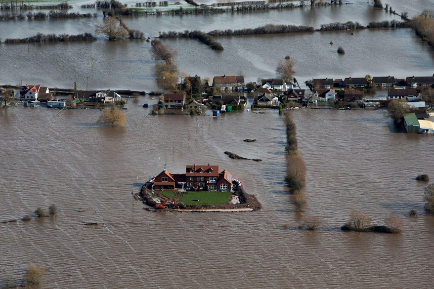 Flood waters inundate the area as one house stands alone and dry near the flooded village of Moorland in Somerset, southwest England, Thursday Feb. 13, 2014.  The house is owned by Sam Notaro, who has built his own levee to hold back the flood waters, as the local communities face further misery in the coming days with heavy rain, wind and snow predicted to sweep across Britain. (AP Photo/Steve Parsons, PA) UNITED KINGDOM OUT - NO SALES - NO ARCHIVES