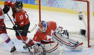 Goalkeeper Anna Prugova of Russia blocks a shot on the goal under pressure from Sara Benz of Switzerland during the 2014 Winter Olympics women's ice hockey game at Shayba Arena, Saturday, Feb. 15, 2014, in Sochi, Russia. (AP Photo/Matt Slocum)