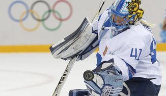 Goalkeeper Noora Raty of Finland reaches for the puck during the 2014 Winter Olympics women's quarterfinal ice hockey game against Sweden at Shayba Arena, Saturday, Feb. 15, 2014, in Sochi, Russia. (AP Photo/Petr David Josek)