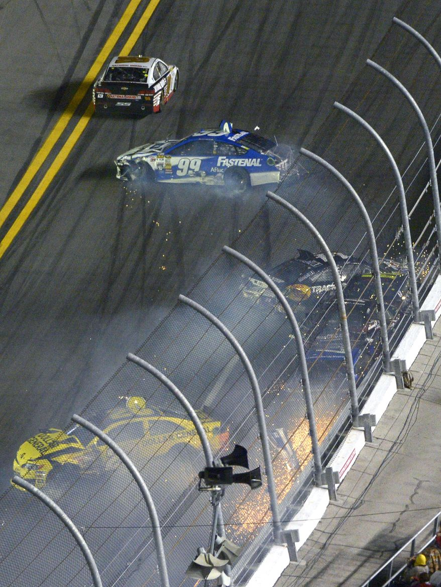 Tony Stewart (14), Jeff Gordon, Kurt Busch and Ricky Stenhouse Jr. (obscured) collide against the wall as Carl Edwards (99) and Matt Kenseth (20) spin out on the front stretch during the NASCAR Sprint Unlimited auto race at Daytona International Speedway in Daytona Beach, Fla., Saturday, Feb. 15, 2014. (AP Photo/Phelan M. Ebenhack)
