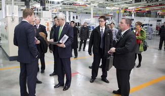 U.S. Secretary of State John Kerry, center left, looks over his notes before delivering remarks on climate change after a tour of the Foton Cummins Engine plant in Beijing, China Saturday, Feb. 15, 2014. Kerry toured the plant and made remarks on climate change cooperation between the United States and China. (AP Photo/Evan Vucci, Pool)