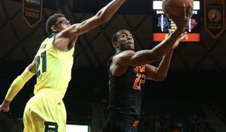 Oklahoma State guard Markel Brown (22), right, scores over Baylor center Isaiah Austin (21), left, in the first half of an NCAA college basketball game, Monday, Feb. 17, 2014, in Waco, Texas. (AP Photo/Waco Tribune Herald, Rod Aydelotte)