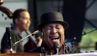 FILE - In this May, 4, 2013, file photo, jazz pianist George Duke performs with bassist Stanley Clarke, background, at the New Orleans Jazz and Heritage Festival in New Orleans. Singer Al Jarreau and bassist Stanley Clarke will celebrate the legacy of their friend and musical partner Duke on the opening day of the 36th annual Playboy Jazz Festival at the Hollywood Bowl. (AP Photo/Gerald Herbert, File)