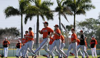 Baltimore Orioles pitchers and catchers warm up during a workout at the team's baseball spring training facility in Sarasota, Fla., Saturday, Feb. 15, 2014. The Orioles first full squad workout is set for Tuesday, Feb. 18. (AP Photo/Gene J. Puskar)