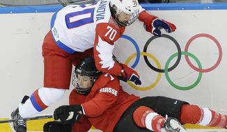 Anna Shibanova of Russia and Lara Stalder of Switzerland collide during the 2014 Winter Olympics women's ice hockey quarterfinal game at Shayba Arena, Saturday, Feb. 15, 2014, in Sochi, Russia. (AP Photo/Matt Slocum)